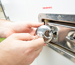 hand turning a key to a lock on a CAPSULE container